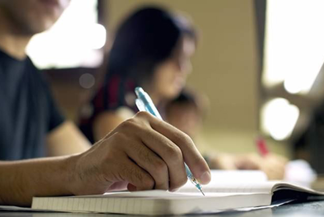 """""""Students doing homework and preparing exam at university, closeup of young man writing in college library"""""""