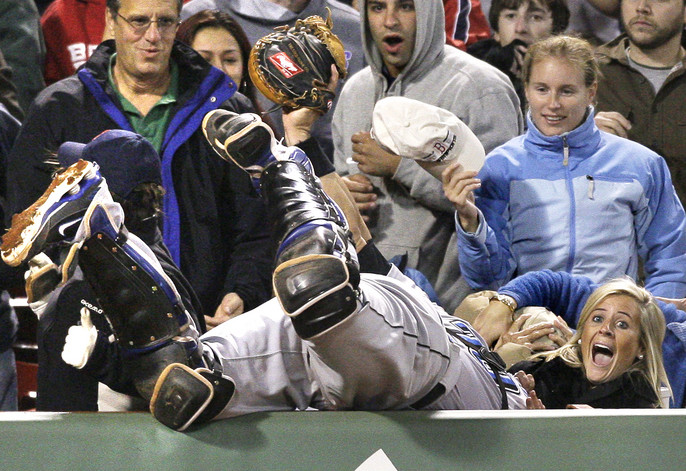 Fans react as Toronto Blue Jays catcher Rod Barajas dives over the wall to catch a foul pop by Boston Red Sox's George Kottaras during the seventh inning in a baseball game at Fenway Park in Boston on Wednesday, Sept. 30, 2009. (AP Photo/Elise Amendola)