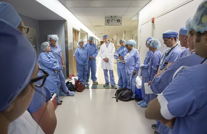 In this June 10, 2016 photo provided by the Mayo Clinic, a medical team of about 60 doctors, nurses, anesthesiologists and others at Mayo Clinic gather before performing the first face transplant surgery at their hospital in Rochester, Minn. Mardini and his team devoted more than 50 Saturdays over 3 1/2 years to rehearsing the procedure, using sets of cadaver heads to transplant the face of one to another. They used 3D imaging and virtual surgery to plot out the bony cuts so the donor's face would fit perfectly on Andy Sandness. (Michael Cleary/Mayo Clinic via AP)