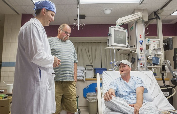"""In this June 10, 2016 photo provided by the Mayo Clinic, Andy Sandness, right, talks with his father, Reed Sandness, and Dr. Samir Mardini, left, before Andy's face transplant procedure at the Mayo Clinic in Rochester, Minn. In the process leading up to the surgery, Mardini tried to temper his patient's enthusiasm. """"Think very hard about this,"""" he said. Only a few dozen transplants have been done around the world, and he wanted Andy to understand the risks and the aftermath: a lifelong regimen of anti-rejection drugs. But Sandness could hardly contain himself. """"How long until I can do this?"""" he asked. (Eric M. Sheahan/Mayo Clinic via AP)"""