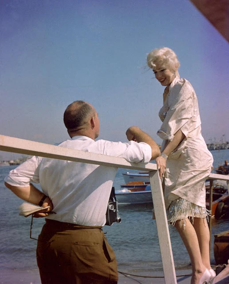 """Das kurvenreiche Filmidol der 50-er Jahre, die US-amerikanische Schauspielerin Marilyn Monroe, bei Dreharbeiten zu der Billy-Wilder-Komödie """"Manche mögens heiss"""" im Jahre 1959 mit einem Fotografen an einem Steg."""