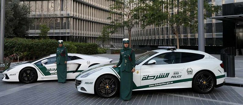 Emirati female police officers pose in front of Ferrari (R) and Lamborghini (L) police vehicles at the foot of the Burj Khalifa tower in the Gulf emirate of Dubai on April 25, 2013. Dubai police showed off a new Ferrari they will use to patrol the city state, hot on the heels of a Lamborghini which joined the fleet earlier. AFP/PHOTO KARIM SAHIB