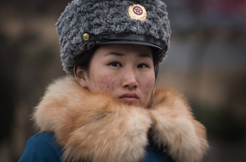 In a photo taken on December 2, 2016 a female traffic police officer directs traffic on a road in Pyongyang. Believed to be hand-picked for their looks, Pyongyang's female traffic police are a familiar sight at intersections around the capital, where traffic volumes have noticeably increased in recent years. / AFP PHOTO / Ed JONES