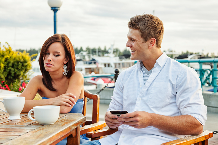 Photo a young couple having a disasterous date.  Young woman looks annoyed as her date seems more excited about his phone than he is about being with her.
