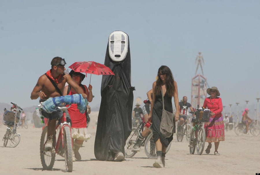 FILE -In this file photo taken Thursday, Aug. 28, 2008, Burning Man participants walk on the playa at the Black Rock Desert near Gerlach, Nev. A California man is appealing the U.S. Bureau of Land Management's decision to increase the Burning Man festival's attendance cap in the Nevada desert. Christopher Brooks' appeal of the agency's increase in the maximum crowd size from 50,000 to 60,900 will be considered by the Interior Board of Land Appeals.(AP Photo/Brad Horn, File)